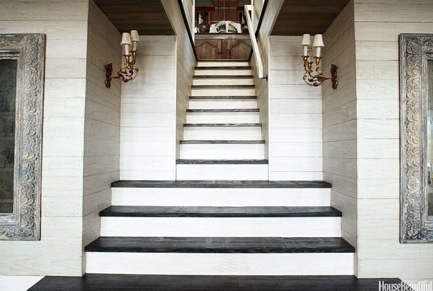 Light and dark wood make a beautiful pairing on a staircase that links the main floor of a four-story Alabama lake house to the bedrooms. Designer Susan Ferrier used the same finishes throughout the house. Walls are whitewashed, rough-cut pine planks. Steps are in a dark Jacobean stain.