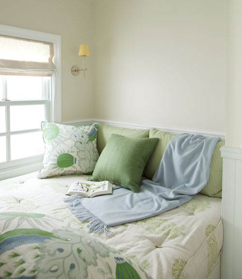 window seat with green linens
