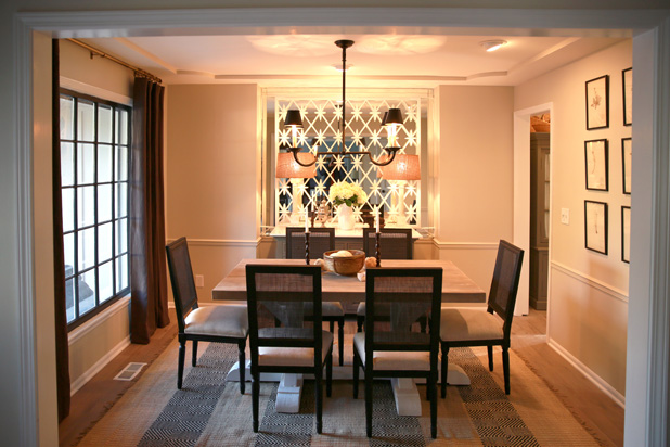 """The dining room was a total bonus,"" says Nate, who notes that the room previously had been used as a playroom for the boys. ""I found a salvage iron gate and placed it over the mirror, and we painted the window frames black. The curtains are from Restoration Hardware, and the accessories are all vintage."""