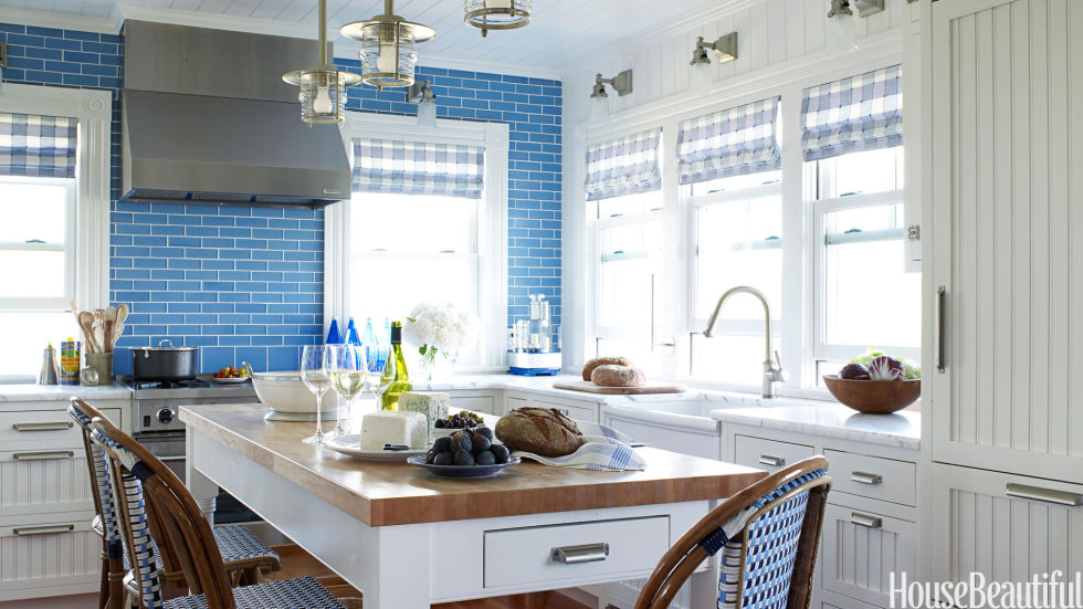 A blue tile backsplash takes over one whole wall in this Fire Island kitchen designed by Marshall Watson. Veneto glass tiles from Stone Source.