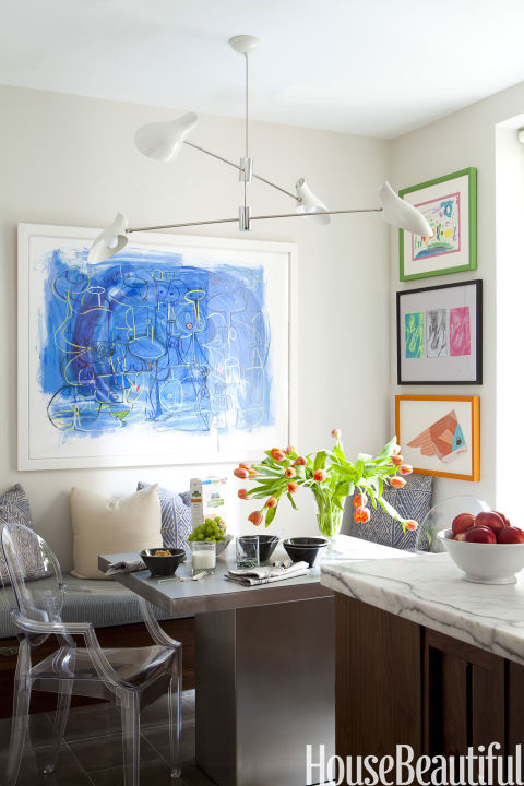 "Children's art projects are given the artist treatment with frames in this Park Avenue apartment's kitchen. ""I thought the apartment should reflect the fact that it's for a young, modern family with three children and a broad, cosmopolitan view of the world,"" says designer Eric Cohler. ""We wanted it to be open, bright, fresh — everything it wasn't."" A David Weeks lighting fixture animates the corner."