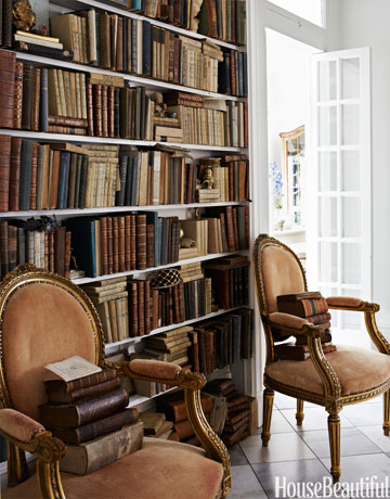 In the library of designer Annie Brahler's Illinois house, antique fauteuils stand against a bookcase made from a salvaged door surround.