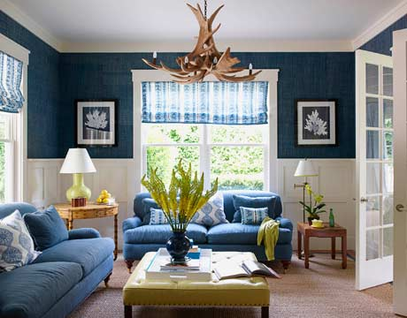 """With four young children, durability in the family room was key for the owners,"" Braff says. ""The dark blue on the sofas, the leather ottoman, and the sisal rug are practically bulletproof."" The sofa is upholstered in Hinson's Rawlston in Dunham Blue. Walls are covered in Africa Raffia in Key West Teal by Phillip Jeffries. The Farra Cocktail ottoman is by Hickory Chair; table lamp is by Christopher Spitzmiller."