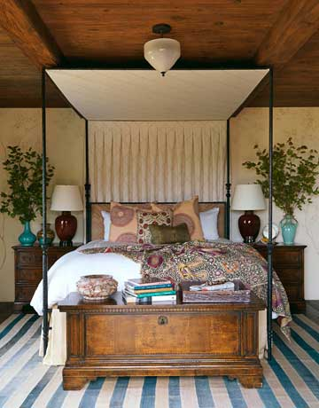 In the guest bedroom, a tracery of branches painted on the plaster walls softens the strong lines of the rustic beams and the iron bed. The trellis pattern on the canopy — Dedar Nomade in Magnolia — adds another dimension.