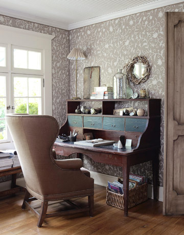 An antique French writing table is paired with a wing chair from Interior Philosophy.