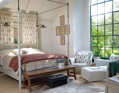 "No curtains required in the master bedroom: The garden screens the room from view. Brinson added steel testers, to raise the bed height, and designed adjustable clip-on reading lights. Bed curtains are in Les Indiennes' Indian Flower: ""I think simple nature-based patterns are the most restful."" The duvet is protected with a no-frills vintage French sheet: ""Sometimes we have three dogs watching TV with us — I have to be able to launder easily!"""