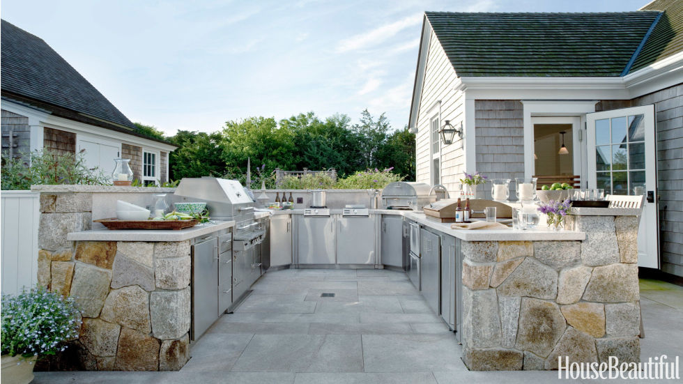 "The U-shaped layout of a Nantucket kitchen is zoned from hot to cold, moving from the grill on the left to two refrigerator drawers and an ice maker on the right. ""Usually an outdoor kitchen is more of an adjunct, but this is complete,"" designer Kris Horiuchi says. ""The client wanted the whole shebang — grill, cooktops, refrigerator, sink, pizza oven."""
